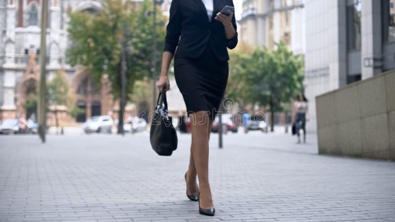 Empresaria que camina para trabajar y que usa el smartphone, forma de vida ocupada en ciudad grande fotografía de archivo