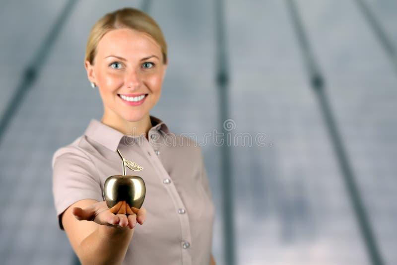 Empresaria que coloca y que sostiene la manzana de oro en su mano imagenes de archivo