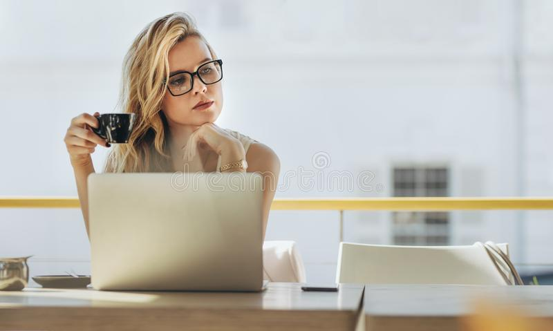 Empresaria que come café y que piensa en el café fotos de archivo libres de regalías
