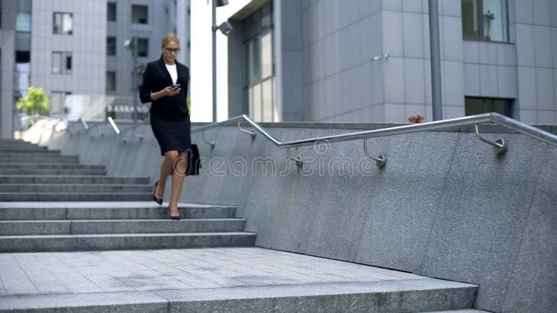 Empresaria que comprueba el correo en el smartphone, caminando abajo de las escaleras, trabajoadicto imagen de archivo