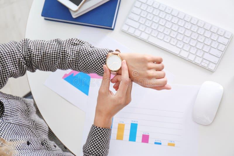 Empresaria que comprueba el tiempo en su reloj en el lugar de trabajo, visión superior Gestión de tiempo imagen de archivo libre de regalías