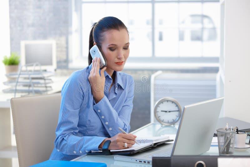 Empresaria que concentra en llamada de teléfono imagenes de archivo