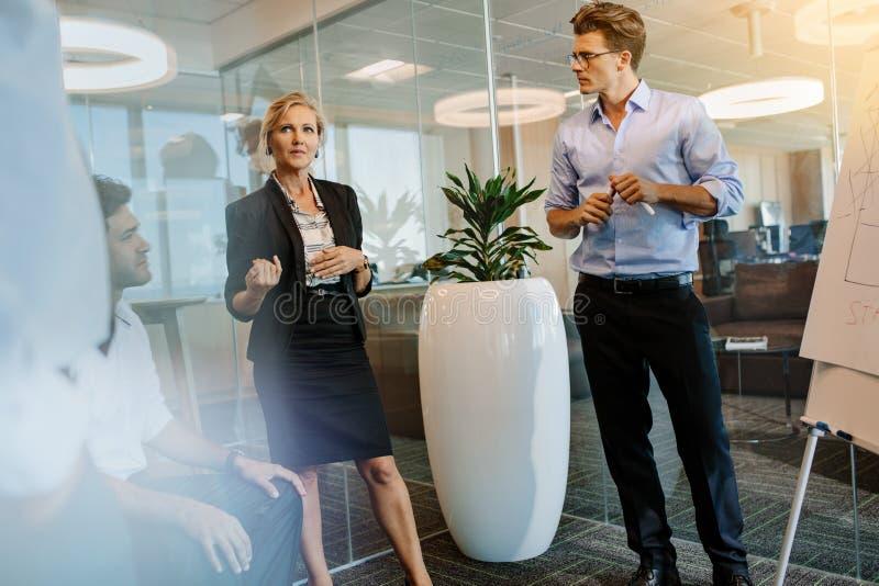 Empresaria que discute con los colegas durante la presentación imagen de archivo