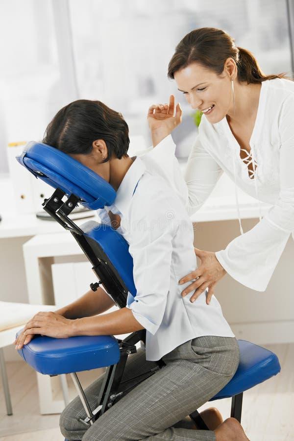 Empresaria que disfruta de masaje en oficina