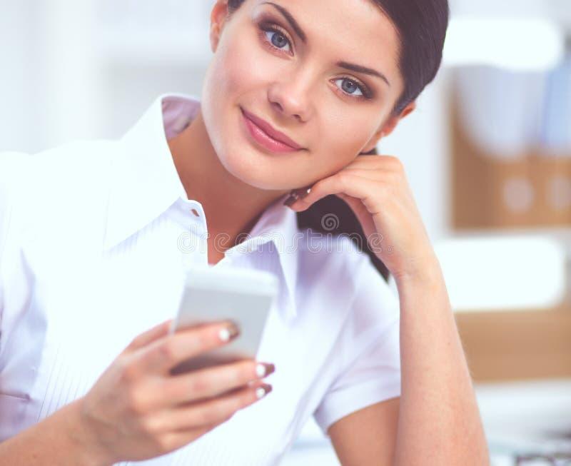 Empresaria que envía el mensaje con el smartphone que se sienta en la oficina foto de archivo