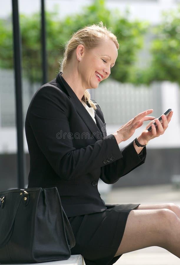 Empresaria que envía el mensaje del teléfono móvil imagen de archivo libre de regalías
