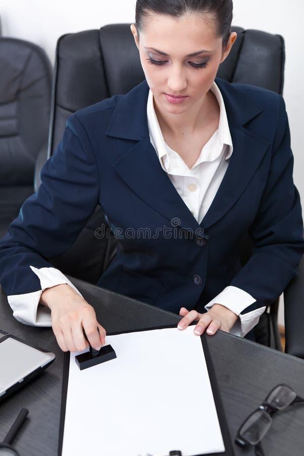 Empresaria que estampa documentos fotografía de archivo