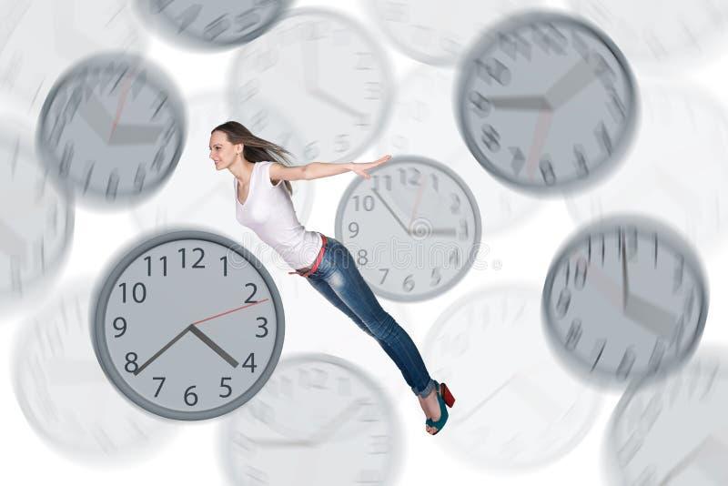 Empresaria que flota entre los relojes imagen de archivo libre de regalías