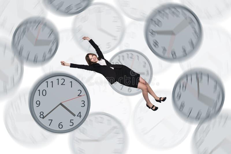 Empresaria que flota entre los relojes imagen de archivo