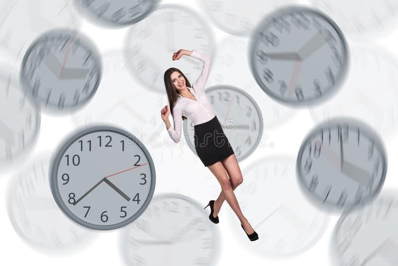Empresaria que flota entre los relojes fotografía de archivo