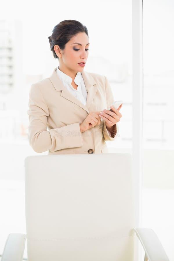 Empresaria que frunce el ceño que se coloca detrás de su silla que manda un SMS en ella foto de archivo libre de regalías