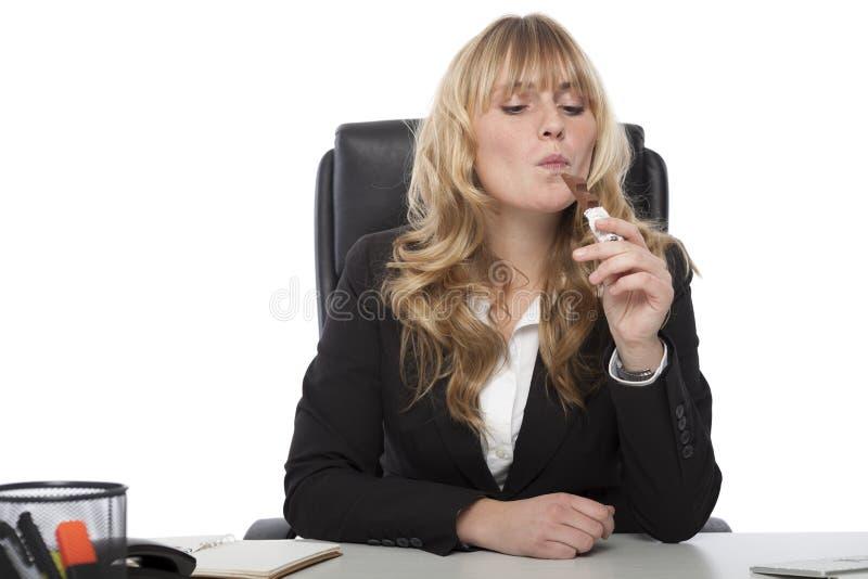 Empresaria que goza de una barra de chocolate en el trabajo fotos de archivo