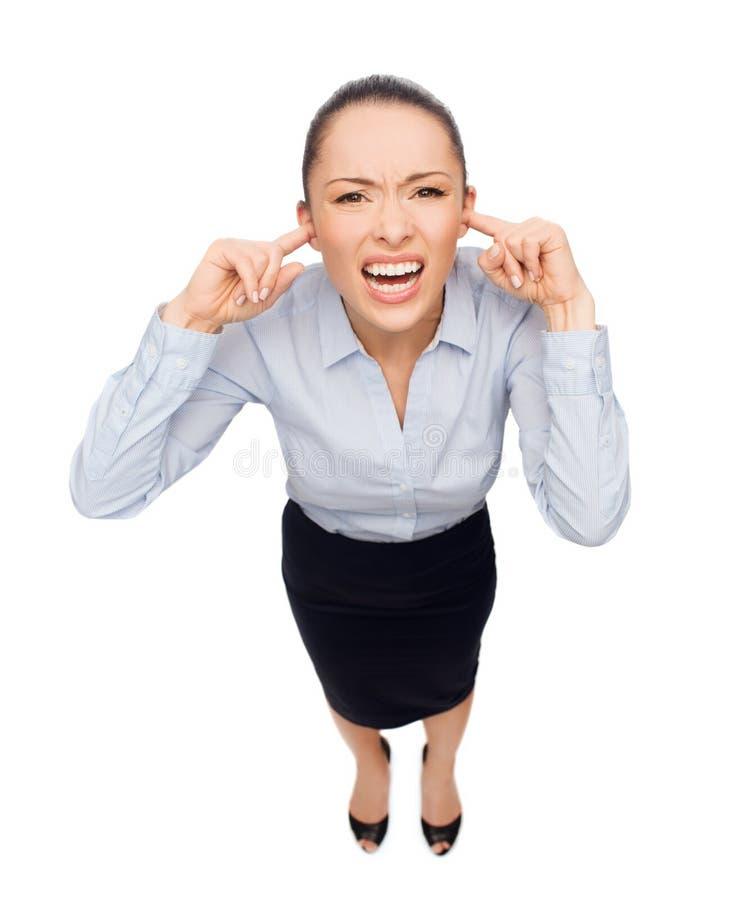 Empresaria que grita con los oídos cerrados imagen de archivo libre de regalías