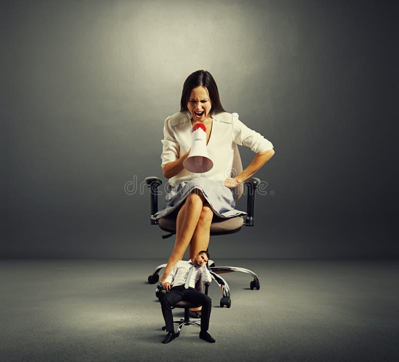 Empresaria que grita en el pequeño hombre de negocios cansado imágenes de archivo libres de regalías