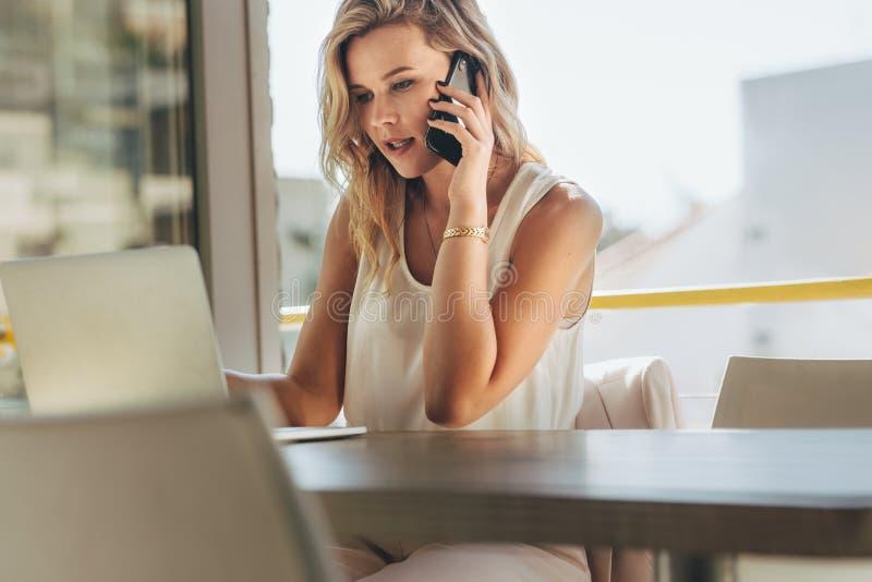 Empresaria que habla con el cliente sobre el teléfono en café fotos de archivo libres de regalías