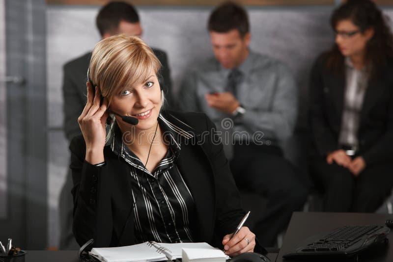 Empresaria que habla en el receptor de cabeza imagenes de archivo