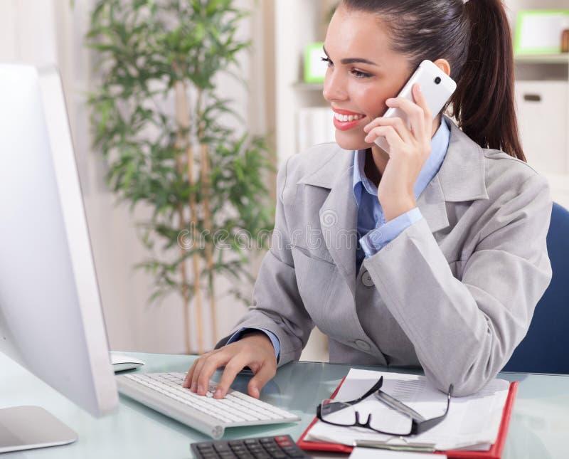 Empresaria que habla en el teléfono en oficina y que trabaja en los comp fotografía de archivo