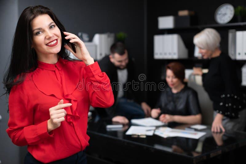 Empresaria que habla en el teléfono en el fondo de los oficinistas que discuten proyecto imagenes de archivo