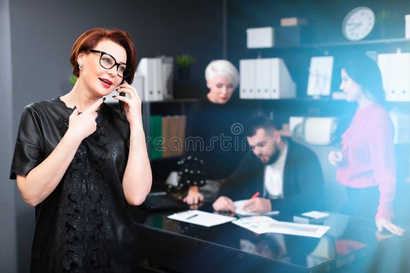 Empresaria que habla en el teléfono en el fondo de los oficinistas que discuten proyecto fotos de archivo libres de regalías