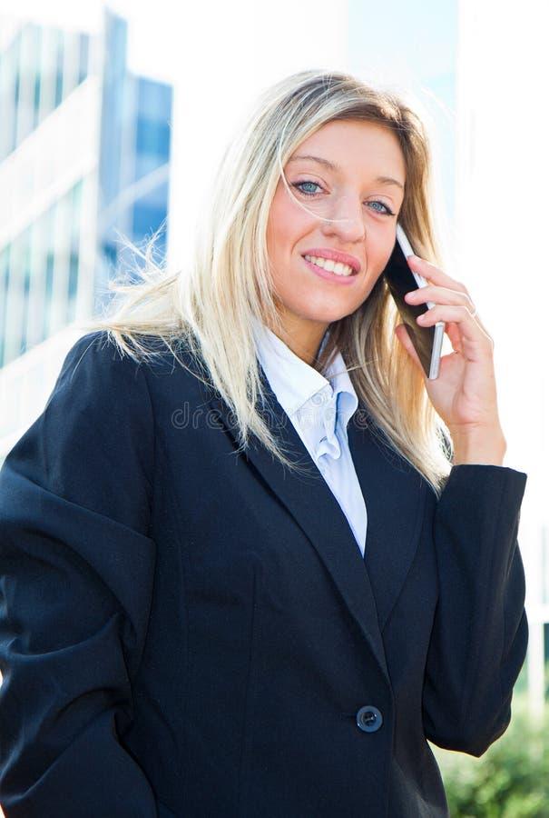 Empresaria que habla en el teléfono móvil fotografía de archivo