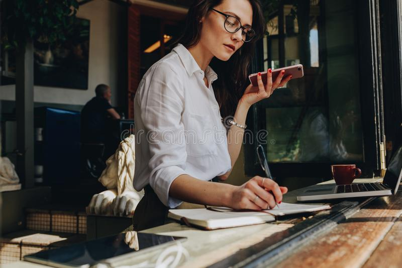 Empresaria que habla en el teléfono y que hace notas en el café imagenes de archivo