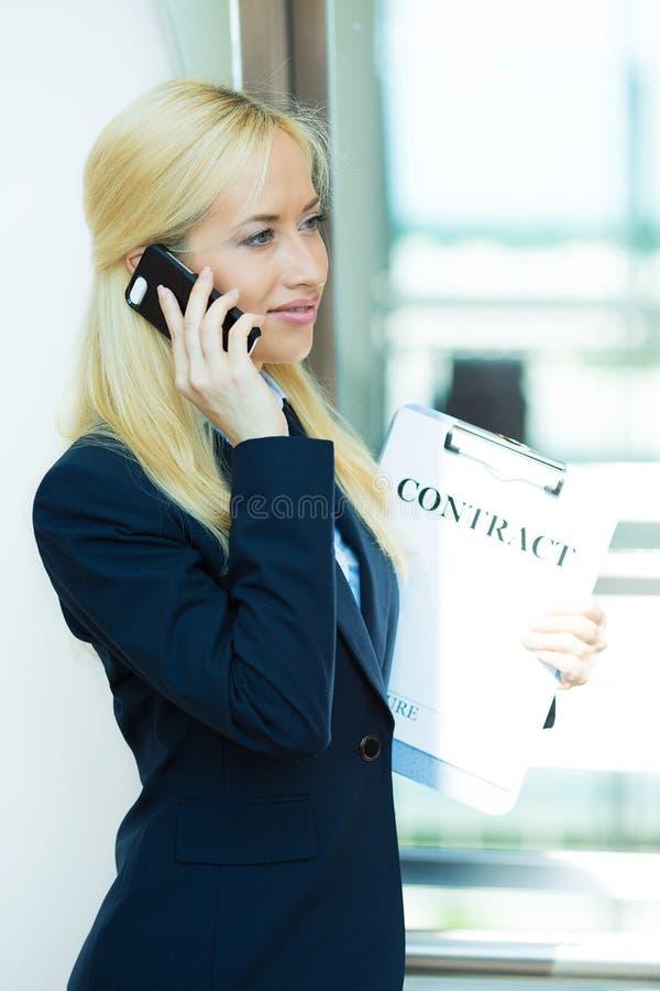 Empresaria que habla en un teléfono, llevando a cabo documentos del contrato fotos de archivo libres de regalías