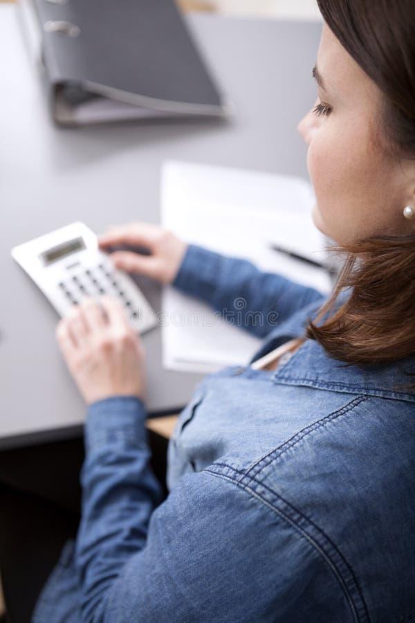 Empresaria que hace cálculos en su escritorio foto de archivo