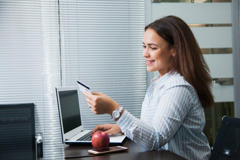 Empresaria que hace compras en línea en su espacio de trabajo en la oficina fotos de archivo