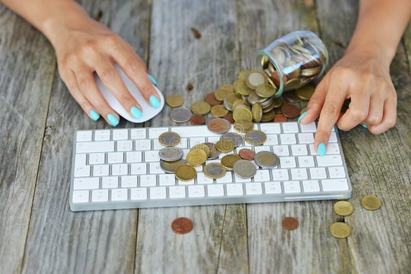 Empresaria que hace el dinero en línea, con las monedas del efectivo en el teclado de ordenador, concepto en línea de la transacc imagenes de archivo