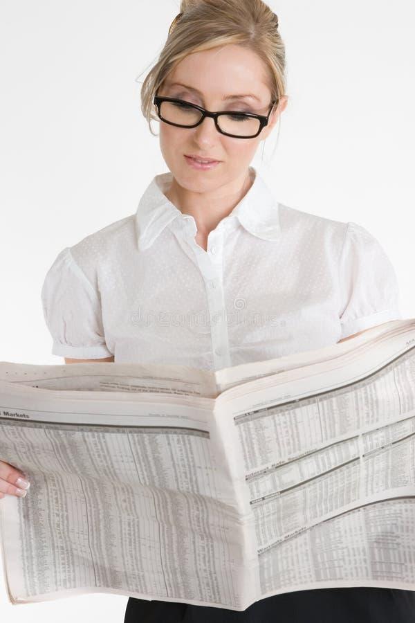 Empresaria que lee el periódico financiero imagen de archivo libre de regalías