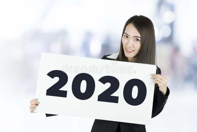Empresaria que lleva a cabo carteles con la muestra 2020 imagenes de archivo