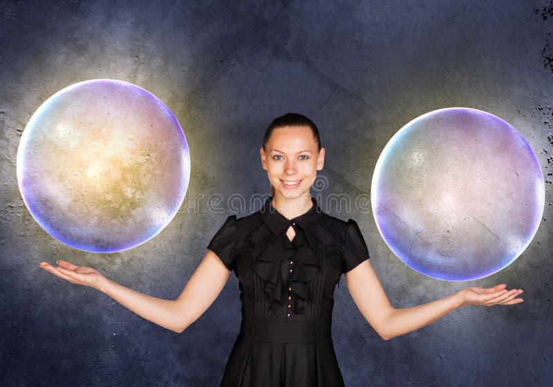 Empresaria que lleva a cabo dos burbujas grandes imágenes de archivo libres de regalías