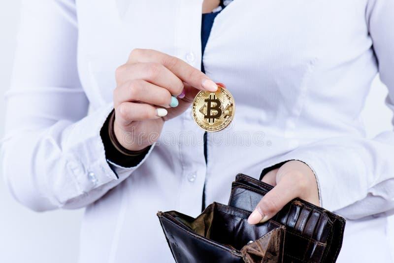 Empresaria que lleva a cabo el bitcoin aislado en un fondo blanco El bitcoin de oro acuña en manos del ` s de las mujeres Moneda  fotos de archivo