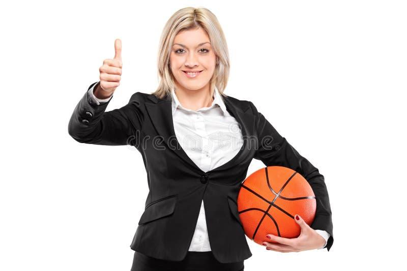 Empresaria que lleva a cabo un baloncesto con los pulgares para arriba fotografía de archivo libre de regalías