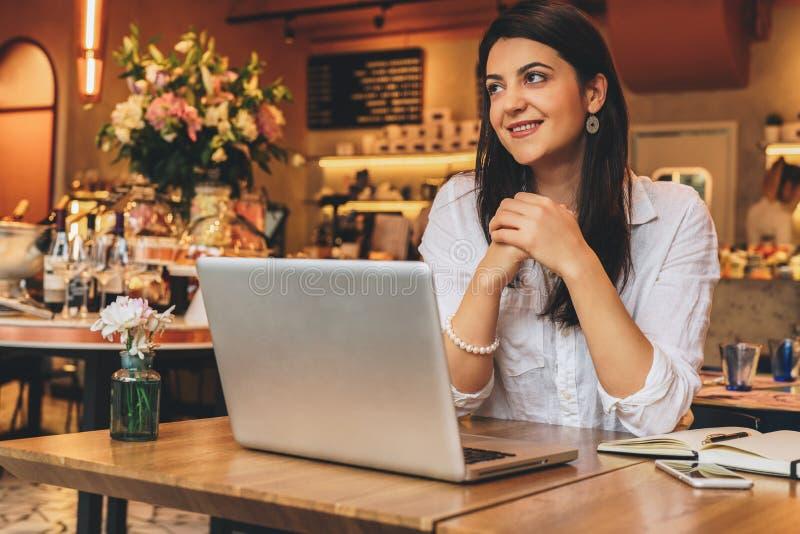 Empresaria que lleva en la camisa que se sienta en café en la tabla, mirando la ventana y la sonrisa En el escritorio es el orden fotos de archivo libres de regalías