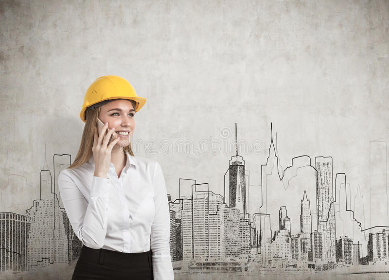 Empresaria que lleva un casco amarillo y que habla en su smartphone mientras que se coloca cerca de un muro de cemento con un pan fotografía de archivo libre de regalías