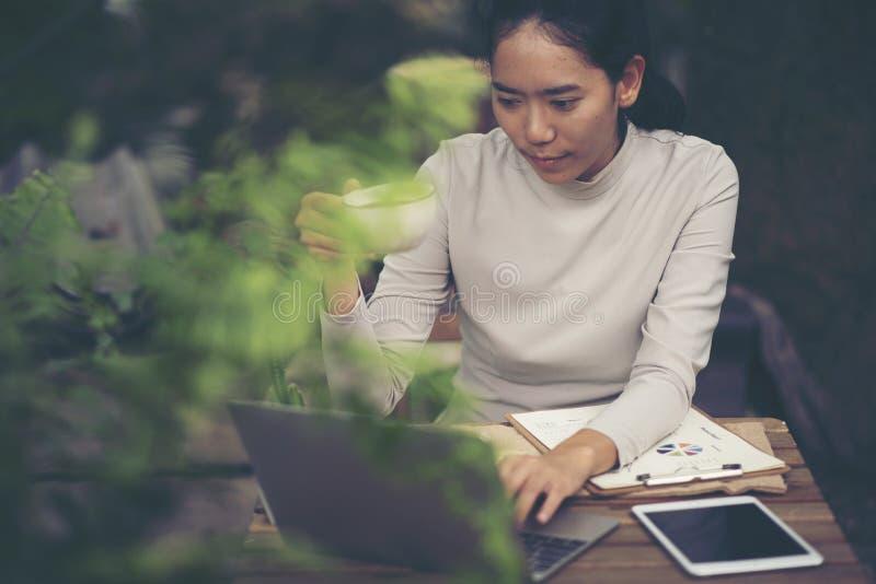 Empresaria que mecanografía en el ordenador portátil en la mujer del lugar de trabajo que trabaja en hom fotos de archivo