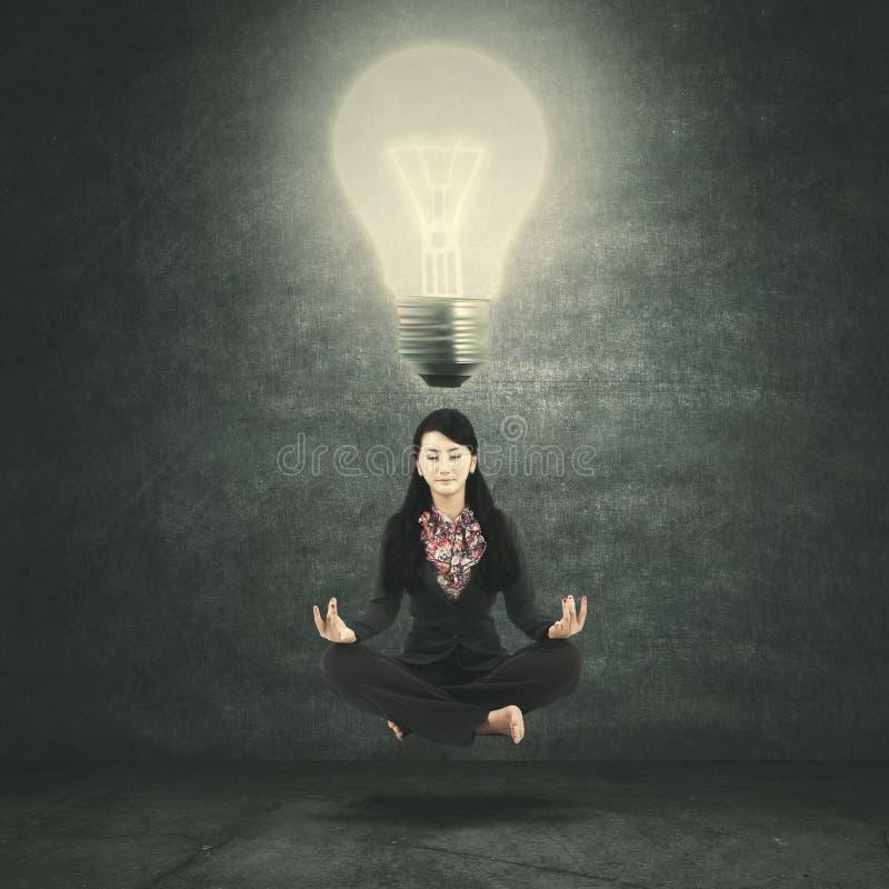 Empresaria que medita debajo de un bulbo brillante foto de archivo