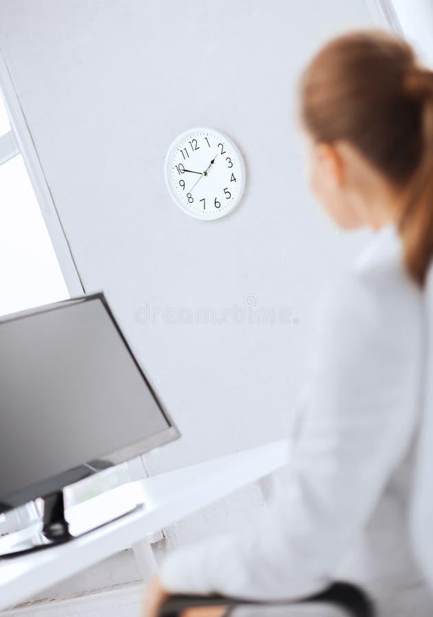 Empresaria que mira el reloj de pared en oficina imagen de archivo libre de regalías