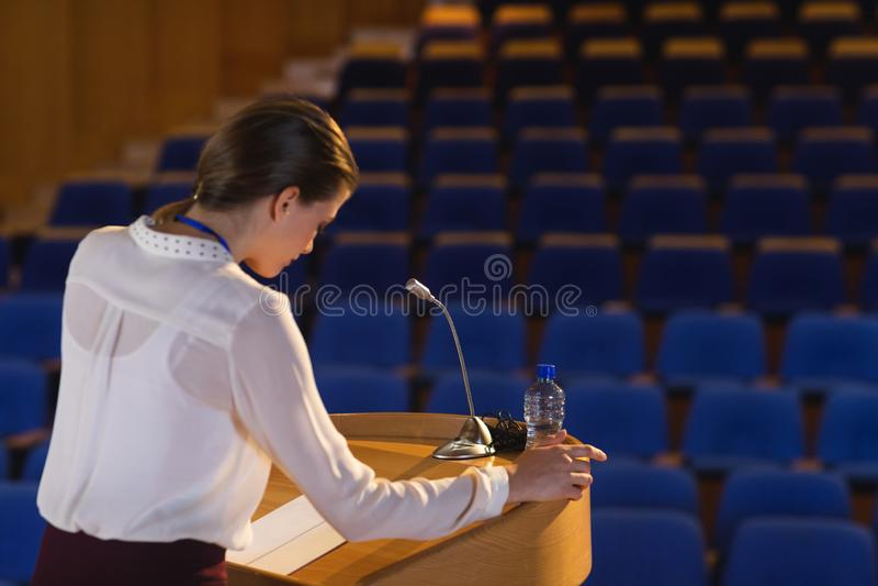 Empresaria que mira en escritura y que intenta hablar en el auditorio vacío fotografía de archivo
