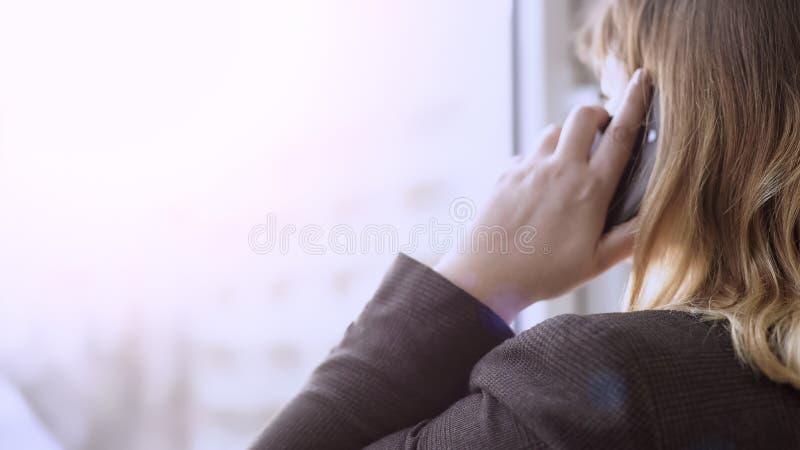 Empresaria que mira fuera de ventana mientras que teniendo conversación sobre el teléfono móvil fotos de archivo libres de regalías