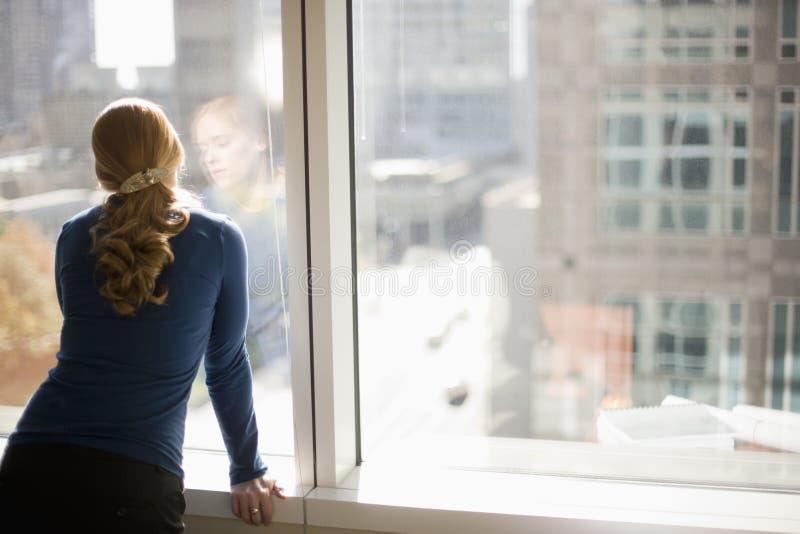 Empresaria que mira hacia fuera la ventana de la oficina fotos de archivo libres de regalías