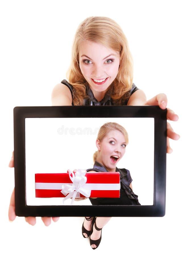 Empresaria que muestra la caja de regalo de la Navidad de la foto del panel táctil de la tableta del ipad imagen de archivo