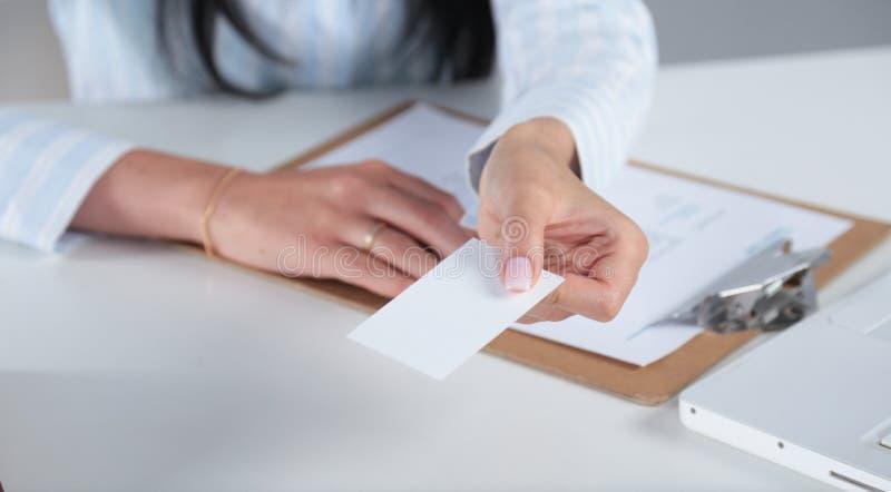Empresaria que muestra y que da una tarjeta de visita en blanco mujer en el traje negro aislado en el fondo blanco foto de archivo libre de regalías