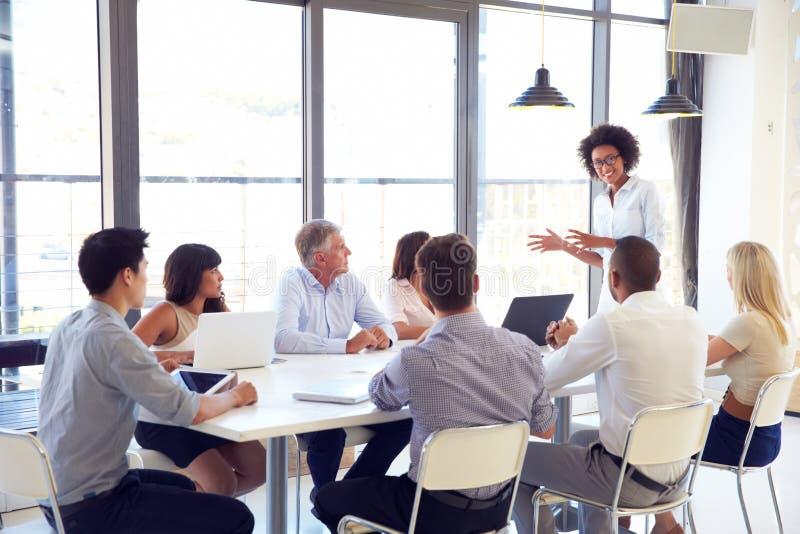 Empresaria que presenta a los colegas en una reunión foto de archivo