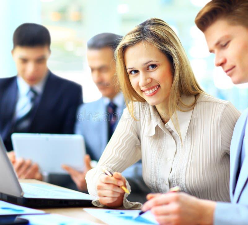 Empresaria que presenta mientras que colegas que hablan junto en oficina brillante foto de archivo libre de regalías