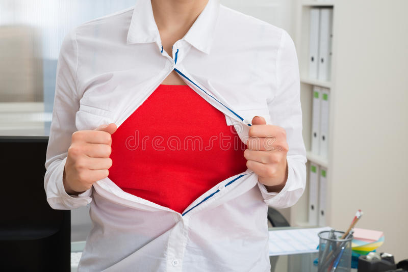 Empresaria que rasga su camisa que muestra el traje rojo foto de archivo libre de regalías