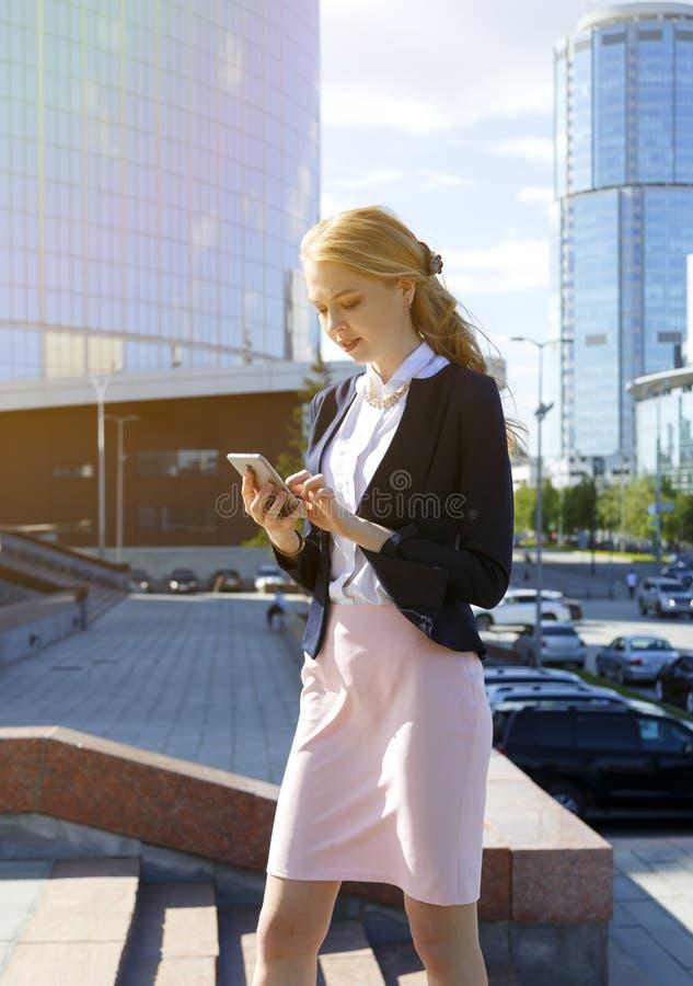 empresaria que recibe malas noticias en mensaje Calle que camina de la señora del negocio durante rotura Mujer que charla, leyend imagen de archivo