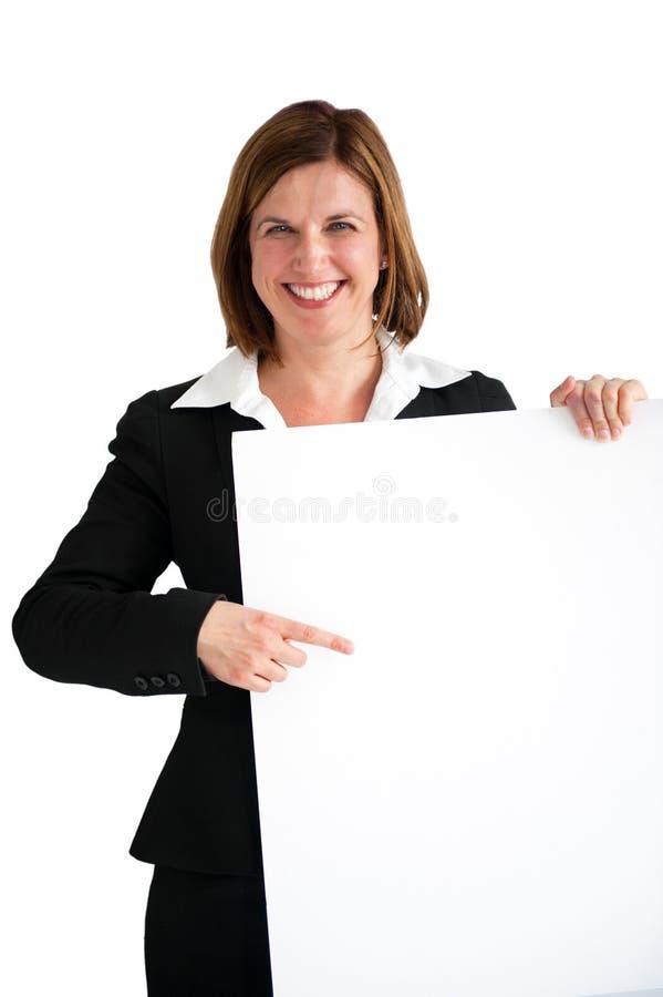 Empresaria que señala al tablero blanco en blanco aislado fotos de archivo