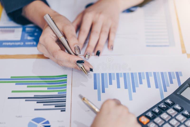 Empresaria que señala la pluma en el documento de negocio en la sala de reunión Cartas y gráficos de los datos de la discusión y  fotografía de archivo